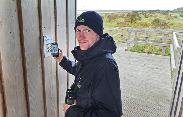 Der Borkumer Nationalpark-Ranger Simon Potthast testet den frisch montierten QR-Code. Foto: Nationalparkverwaltung