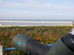 Blick von der Düne auf das Meer. Im Vordergrund steht ein Swarovski-Spektiv